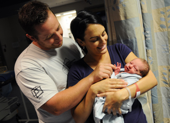 Parents hold their newborn baby