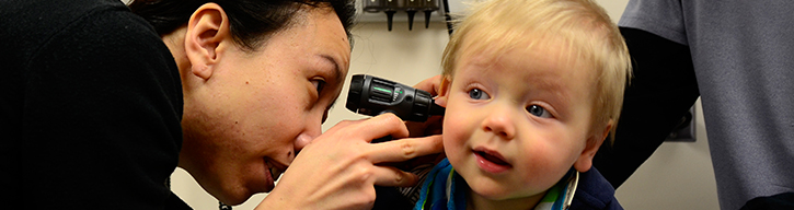 Medical professional looking into toddlers ear with tool